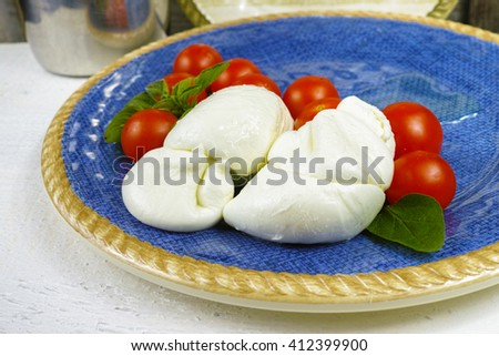 Traditional italian mozzarella buffala with tomatoes and basil on blue plate - stock photo