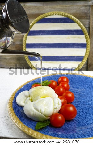 Traditional italian mozzarella buffala with tomatoes and basil on blue plate, copy space - stock photo