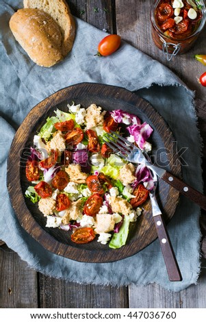 Traditional italian panzanella salad: salad with sun dried tomatoes, green salad leaf, dry ciabatta bread and fresh white cheese served in authentic wooden bowl. Table top view - stock photo