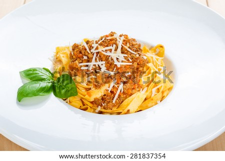 Traditional italian pasta bolognese with minced meat, tomato sauce and parmesan decorated with basil on white round plate closeup - stock photo