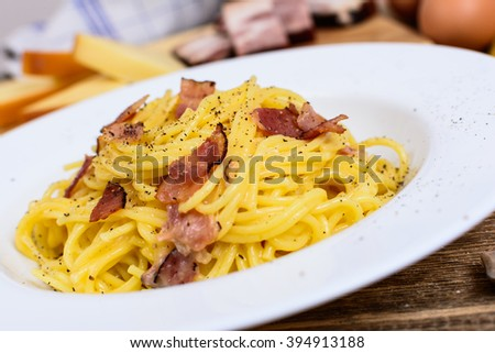 Traditional italian pasta spaghetti alla carbonara with bacon, cheese and agg yolk on white plate - stock photo