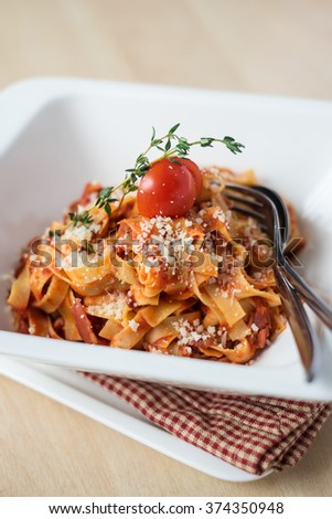 Traditional italian pasta tagliatelle with bolognese sauce or ragu with cherry tomato, thyme and parmesan cheese in a plate, selective focus - stock photo
