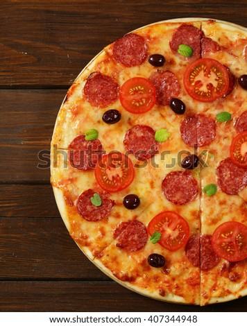 traditional Italian pepperoni pizza with olives and tomatoes