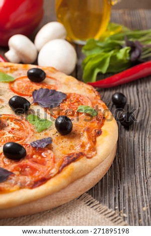 Traditional italian pizza margherita with tomatoes, olives and basil on vintage rustic background