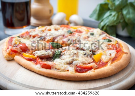 Traditional Italian pizza with cherry tomatoes, pepper, salami and basil on the wooden background. Rustic style. - stock photo