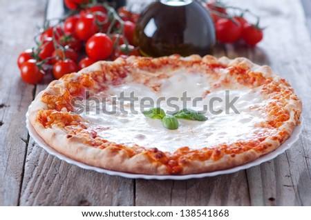 Traditional italian pizza with mozzarella and basil, selective focus - stock photo