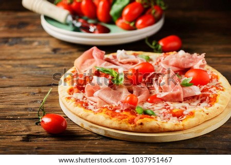 Traditional Italian pizza with mozzarella, tomato and bacon, selective focus and copyspace