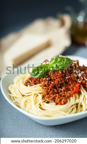Traditional Italian spaghetti Bolognese topped with grated with parmesan cheese sprinkled on a tomato based meat sauce garnished with basil leaves - stock photo