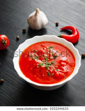 Traditional Italian tomato soup gazpacho in bowl on dark wooden background