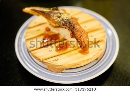 Traditional japanese food, Eel (unagi) Nigiri Sushi or Unagi Kabayaki on wooden dish (shallow dof) - stock photo