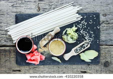Traditional japanese food ingredients: udon noodles, ginger, sesame seeds, soy sauce top view - stock photo