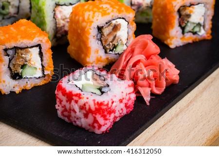 Traditional japanese food, Mix colorful sushi set on wooden  black board. Orange, red sushi rolls, wasabi. Food photography. - stock photo