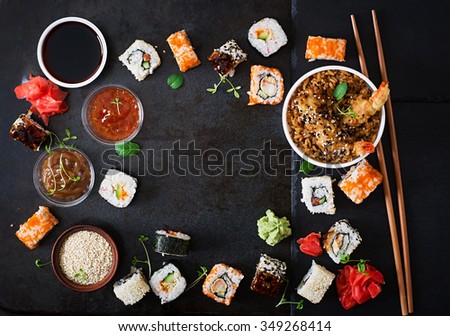 Traditional Japanese food - sushi, rolls, rice with shrimp and sauce on a dark background. Top view - stock photo