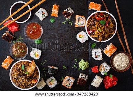Traditional Japanese food - sushi, rolls, rice with shrimp and udon noodles with chicken and mushrooms on a dark background. Top view