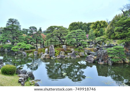 Traditional Japanese Landscape Zen Garden With Large Pond, Ornamental  Stones And Manicured Pine Trees