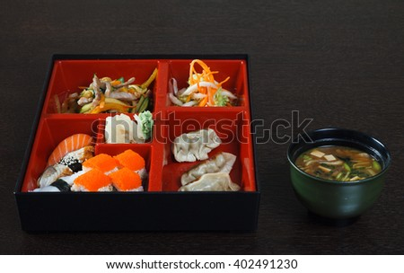 Traditional Japanese lunch of sushi, miso soup, gyoza, tuna, ginger, red caviar, wasabi, the pieces of meat, sashimi and salad. Container with compartments for dishes on a wooden table.  - stock photo