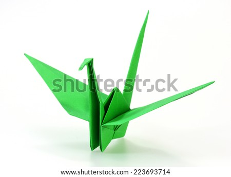 Traditional Japanese origami crane made of green paper over white background - stock photo