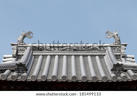 Traditional Japanese temple roof against a blue sky