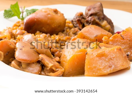Traditional Jewish Cholent (Hamin) prepared is Israel as the main dish for the Shabbat meal made with beef, potato, beans, barley, and more and served with horseradish sauce (Chrein) - stock photo