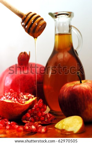 Traditional Jewish food, apple, honey and pomegranate for the holiday of Rosh Hashanah are isolated on white. - stock photo