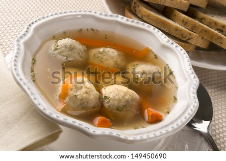 Traditional Jewish passover dish matzah ball soup served with rye bread - stock photo