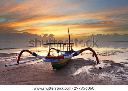 Traditional Jukung boat on Karang beach at sunrise, Bali, Indonesia - stock photo