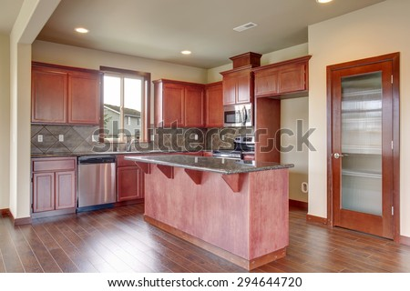 Traditional kitchen with dark hardwood floor, island, and stained cabinets, in luxurious northwest home. - stock photo