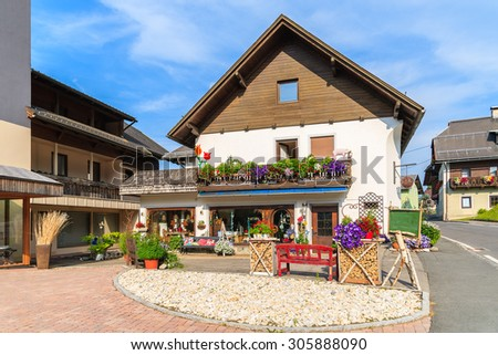 Traditional l alpine houses decorated with flowers on shore of Weissensee lake in summer season, Carinthia land, Austria - stock photo