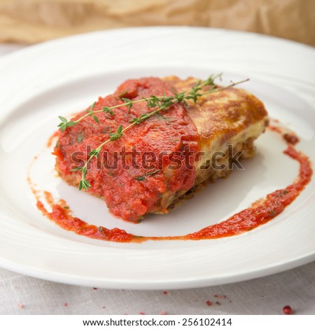 Traditional lasagna made with minced beef bolognese sauce served on a white plate - stock photo