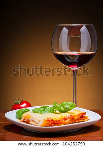traditional lasagna with glass of red wine on a wooden table