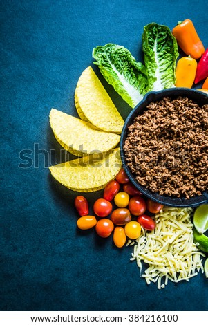 Traditional latin street food, tacos with beef and salad, overhead view on dark slate with space for recipe or copy text. - stock photo