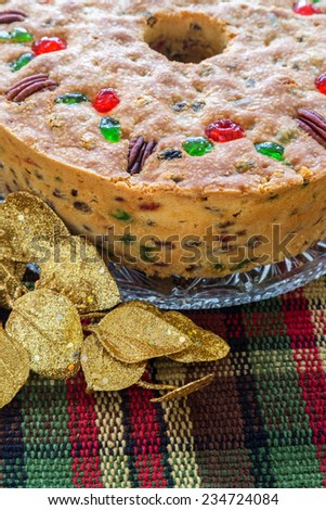 Traditional light fruitcake decorated with pecans and cherries. - stock photo
