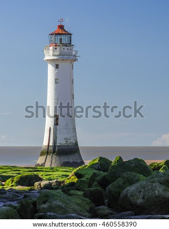 Traditional Lighthouse on rocky and sandy beach (portrait format)