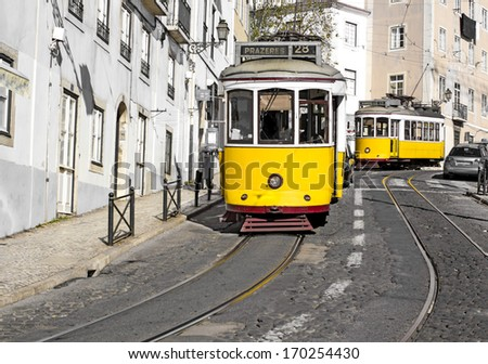 Traditional Lisbon cityscape with yellow trams in action - stock photo