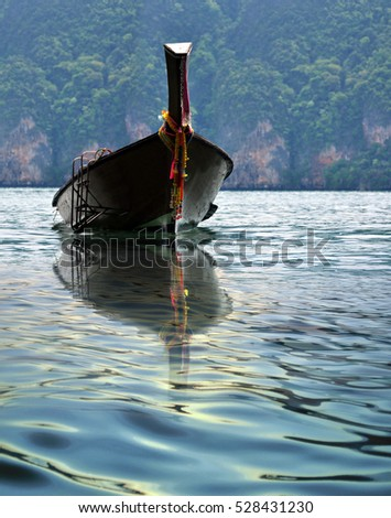traditional long tail wood boat or traditional fishing boat in Thailand decorated with flowers