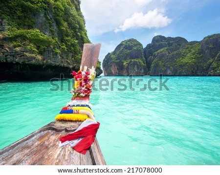 Traditional longtail boat in the turquoise colored waters of Maya Bay, Ko Phi Phi, Thailand. - stock photo