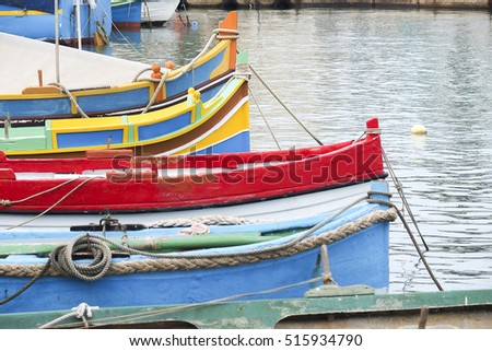 traditional Maltese colored fishing boats luzzu in Marsaxlokk harbor, Malta