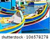Traditional Maltese fishing boats, called Luzzu, in the harbor of Marsaxlokk, Malta. - stock photo