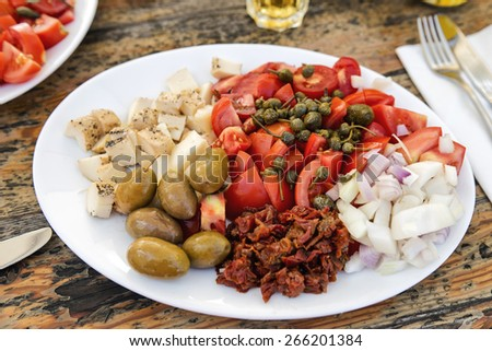 Traditional Maltese plates with different ingredients and with Gbejna,  a small round cheese made in Gozo, Malta.  - stock photo