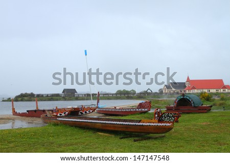 Traditional Maori wood carved canoes on the shore in New Zealand in rainy weather - stock photo