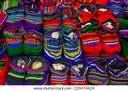 traditional mayan textiles on s msrket stall in antigua guatemala baby shoes - stock photo