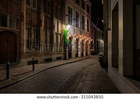 Traditional medieval narrow street of Bruges at night - stock photo