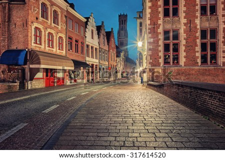 Traditional medieval red and white brickwall architecture of Bruges at twilight with  Belfort on background - stock photo