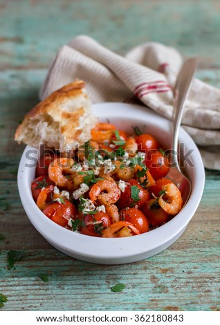 Traditional mediterranean dish with roasted cherry tomatoes, shrimps, salted feta cheese and parsley in a bowl with bread, selective focus