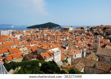 Traditional Mediterranean Old Town houses with red tiled roofs and rocky green idyllic island in background, Dubrovnik, Dalmatia, Croatia, Europe. Beautiful travel photo. - stock photo