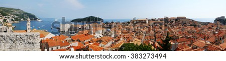 Traditional Mediterranean Old Town houses with red tiled roofs and rocky green idyllic island in background, Dubrovnik, Dalmatia, Croatia, Europe. Beautiful travel photo panorama. - stock photo