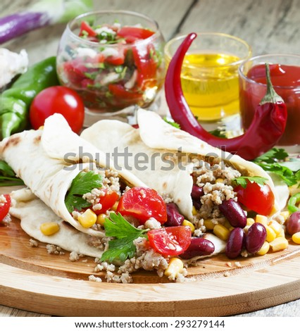 Traditional Mexican burritos with meat and beans, selective focus - stock photo