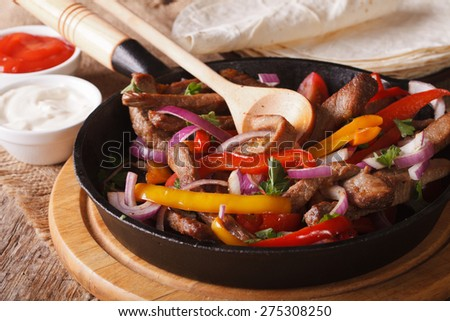 Traditional Mexican fajitas close up on the table. Horizontal rustic style