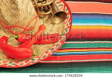 Traditional Mexican fiesta poncho rug in bright colors with sombrero chilli chili background with copy space - stock photo