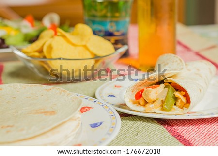 Traditional mexican food in a table, with bowl of nachos, spicy sauce, chicken fajita, tortillas and fresh salad - stock photo